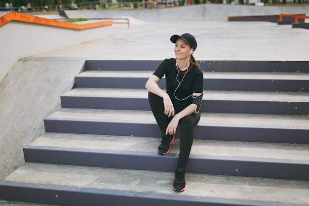 Jonge atletische lachende vrouw in zwart uniform en pet met koptelefoon luisteren naar muziek, rusten en zitten voor of na het hardlopen, trainen op trappen in stadspark buitenshuis