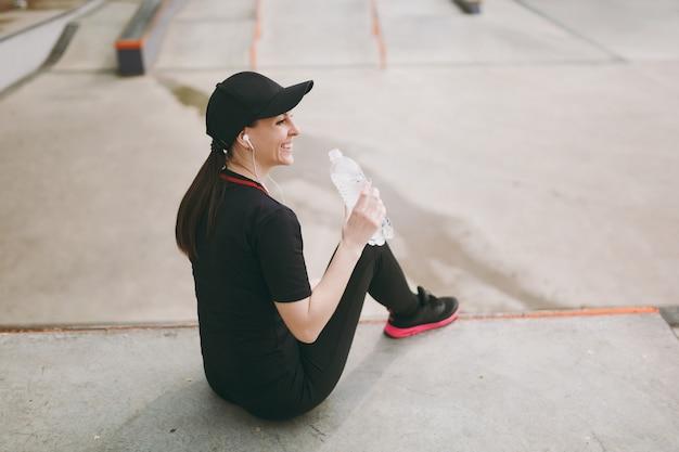 Jonge atletische lachende vrouw in zwart uniform, pet met koptelefoon luisteren naar muziek met fles met water zittend voor of na het hardlopen, training in stadspark buitenshuis