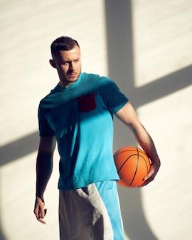 Jonge atletische man basketbalspeler die bal vasthoudt en in de buurt van muur staat met schaduwen van raam