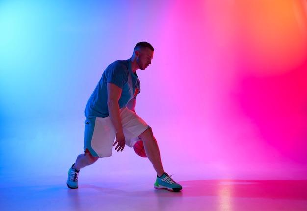 Jonge atletische man basketbalspeler dribbelen met bal op neon blauwe en roze achtergrond