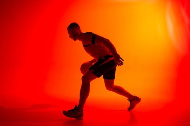 Jonge atletische man basketbalspeler dribbelen met bal op rode en oranje achtergrond