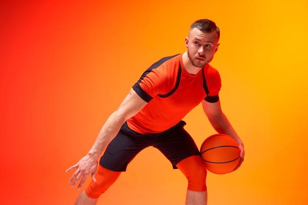 Jonge atletische man basketbalspeler staande met bal in verdedigingspositie op oranje