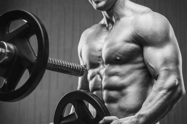 Jonge atletische man die spieren oppompt in de sportschool bij training sport en gezondheidszorg concept pagina