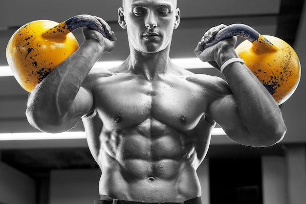 Jonge atletische man die spieren oppompt in de sportschool bij training sport- en gezondheidszorgconcept
