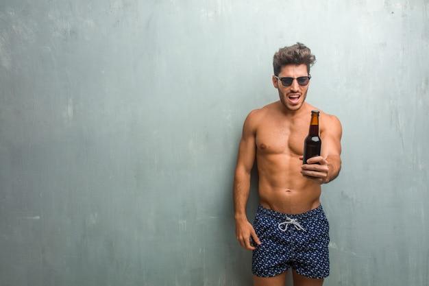 Jonge atletische man draagt een zwembroek tegen een grunge muur erg boos en boos