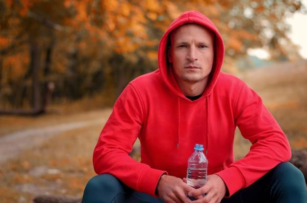 Jonge atletische man in een rood sportjack met capuchon en zwarte sportlegging zit op een logboek en houdt fles met water vast na het hardlopen