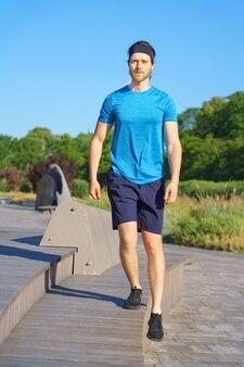 Jonge atletische man in sportkleding die buiten op zonnige zomerdag traint