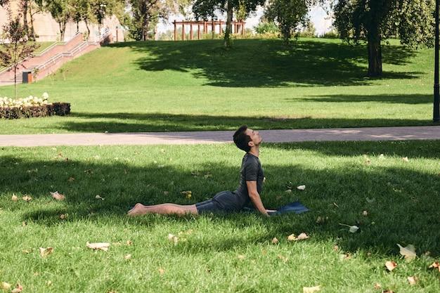 Jonge atletische man in sportkleding die yoga doet in het park. oefen asana buitenshuis. mensen oefenen op groen gras met yoga mat. sterke volwassen blanke man in opwaarts gerichte hond pose