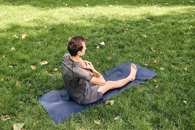 Jonge atletische man in sportkleding die yoga doet in het park. oefen de beenwieg asana buitenshuis. mensen oefenen op groen gras met yoga mat. fitness en gezonde levensstijl.
