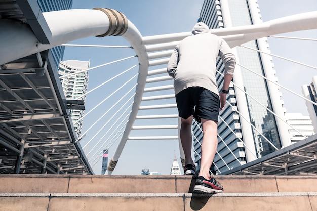 Jonge atletische man joggen op de brug van de stad, sportieve man loopt in de ochtend met stedelijke scène