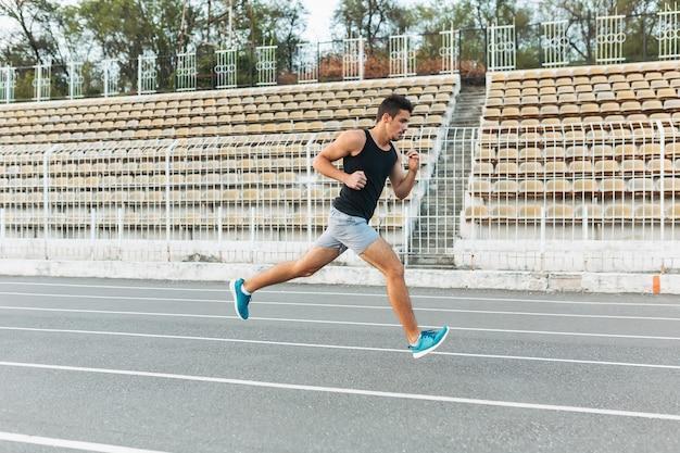 Jonge atletische man loopt op het stadion in de ochtend