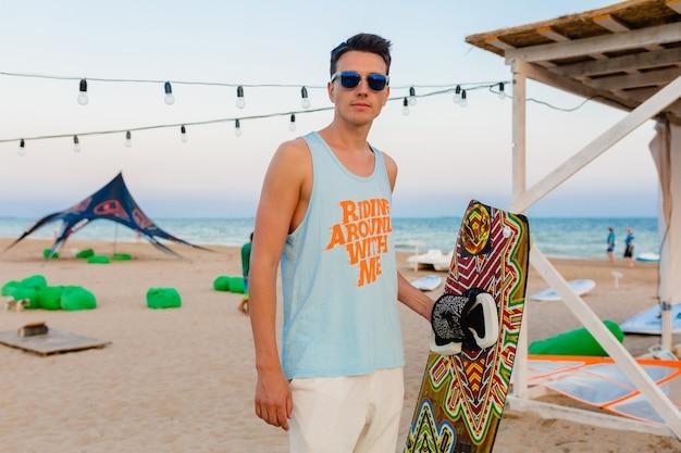 Jonge atletische man met kitesurfplank die zich voordeed op het strand met een zonnebril op zomervakantie