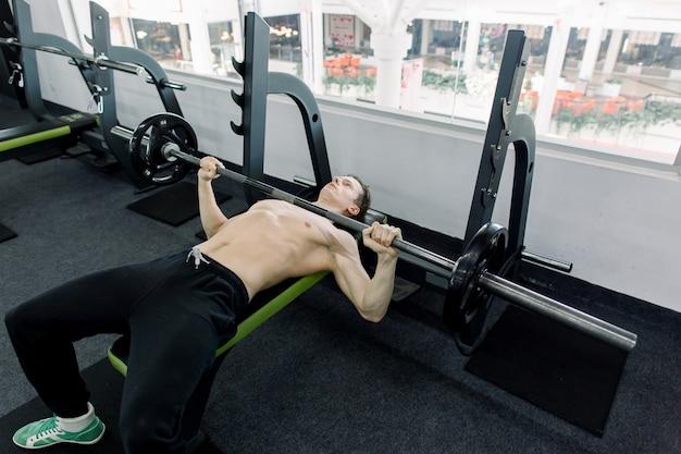 Jonge atletische man oppompen van spieren op bankdrukken in de sportschool. jonge bodybuilder training in de sportschool: borst - halter bankdrukken - brede grip