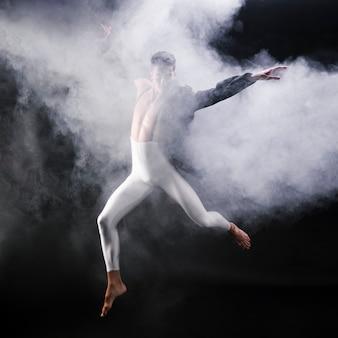 Jonge atletische man springen en dansen in de buurt van rook