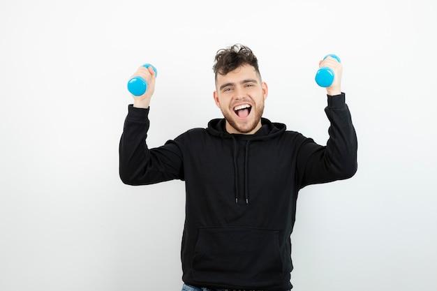 Jonge atletische man training met blauwe halters.