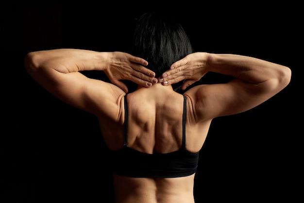Jonge atletische meisje met zwart haar draaide haar rug en het tonen van een gespierde rug en armen