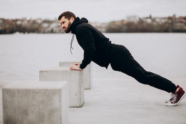 Jonge atletische mens die door de rivier uitoefenen en opdrukoefeningen doen