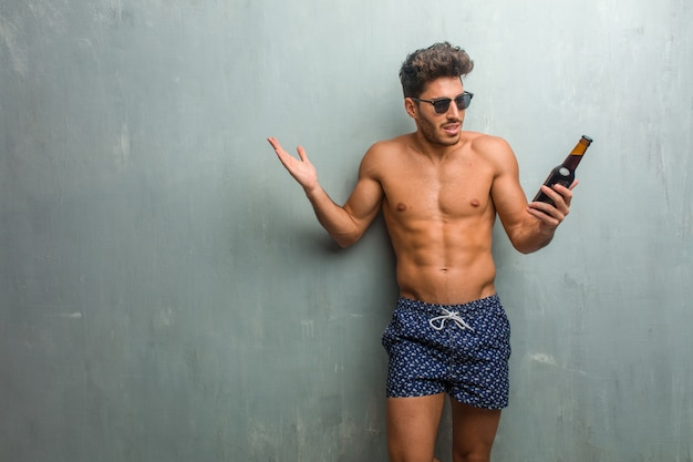 Jonge atletische mens die een zwempak dragen tegen een gekke en wanhopige grungemuur