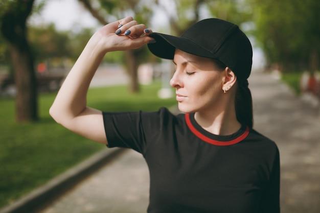 Jonge atletische mooie brunette vrouw in zwart uniform en pet met gesloten ogen staan en houden hand in de buurt van pet op training op pad in stadspark buitenshuis