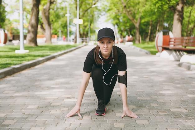 Jonge atletische mooie brunette vrouw in zwart uniform en pet met koptelefoon luisteren naar muziek bij lage start voordat ze rennen, trainen op pad in stadspark buitenshuis