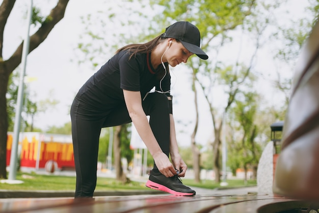 Jonge atletische mooie brunette vrouw in zwart uniform en pet met koptelefoon luisteren naar muziek, schoenveters strikken voordat ze rennen, trainen op bankje in stadspark buitenshuis