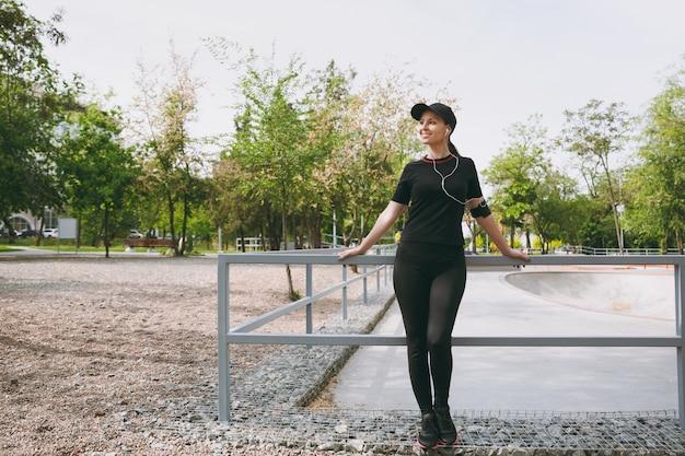 Jonge atletische mooie brunette vrouw in zwart uniform en pet met koptelefoon luisteren naar muziek, staan voor of na het hardlopen, trainen in stadspark buitenshuis