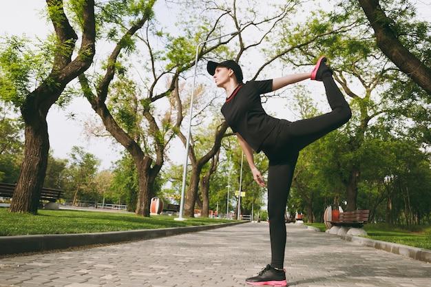 Jonge atletische mooie brunette vrouw in zwart uniform, pet doet sport rekoefeningen, warming-up voor hardlopen of training, staande in stadspark buitenshuis