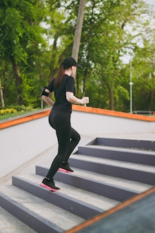 Jonge atletische mooie brunette vrouw in zwart uniform, pet met koptelefoon die sportoefeningen doet, training en hardlopen, traplopen in stadspark buitenshuis Gratis Foto