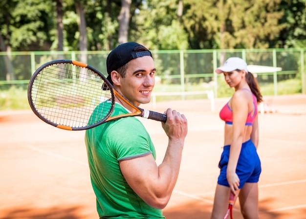 Jonge atletische paar tennissen op de rechtbank.
