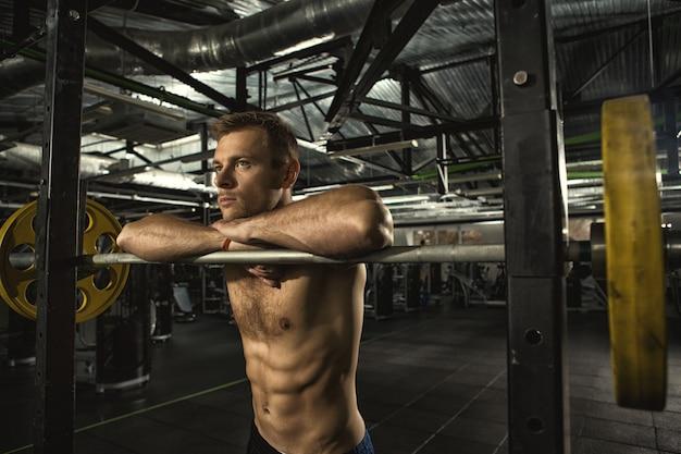 Jonge atletische shirtless man met hete sexy sterk afgezwakt en fit gespierd lichaam op zoek weg denken rustend op de sportschool