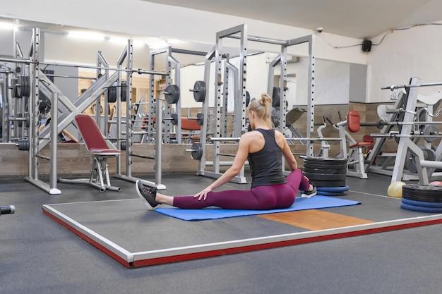 Jonge atletische spiervrouw die uitrekkende training in de gymnastiek doet