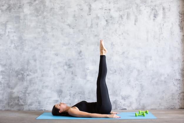 Jonge atletische sportieve slanke vrouw die oefening in gymnastiek doet.