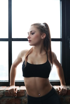 Jonge atletische vrouw die haar oefeningsroutine thuis doet