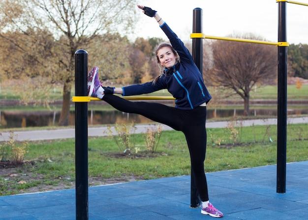 Jonge atletische vrouw die het been uitrekt