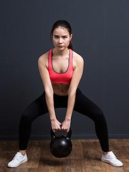 Jonge atletische vrouw die hurkzit met gewichten doet