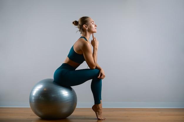 Jonge atletische vrouw die oefeningen op fitball in de gymnastiek doet