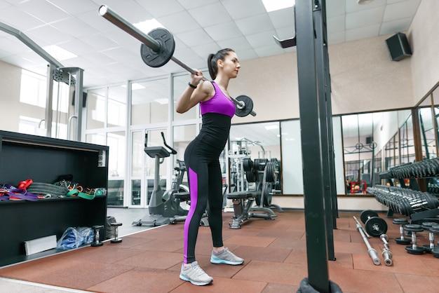 Jonge atletische vrouw die op de machines in moderne sportgymnastiek uitoefenen