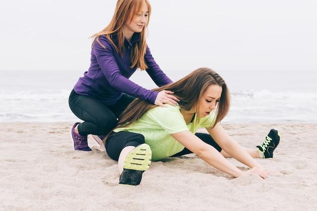 Jonge atletische vrouw die sportenoefeningen op het strand in bewolkt weer doet