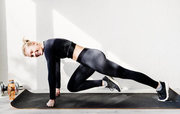 Jonge atletische vrouw die thuis bergbeklimmeroefening uitwerkt