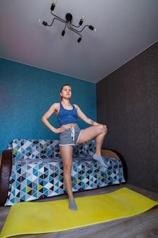 Jonge atletische vrouw die yoga beoefent, lichaam strekken, oefenen, benen naar de zijkant zwaaien, trainen, sportkleding dragen, blauw t-shirt, korte broek, bij de bank thuis