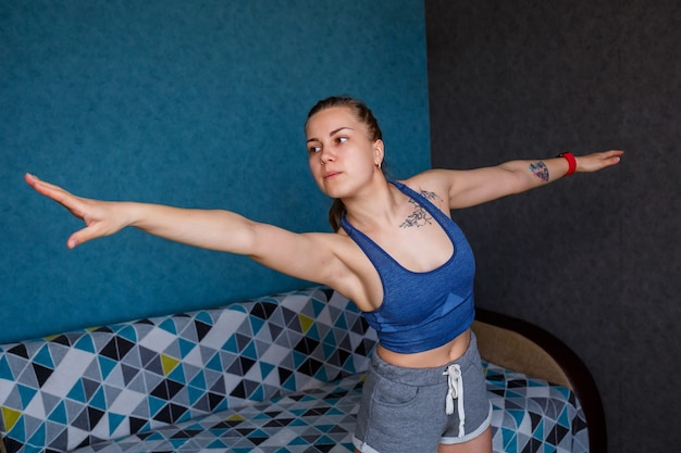 Jonge atletische vrouw die yoga beoefent, lichaam strekken, oefenen, trainen, sportkleding dragen, blauw t-shirt, korte broek, in de buurt van de bank thuis