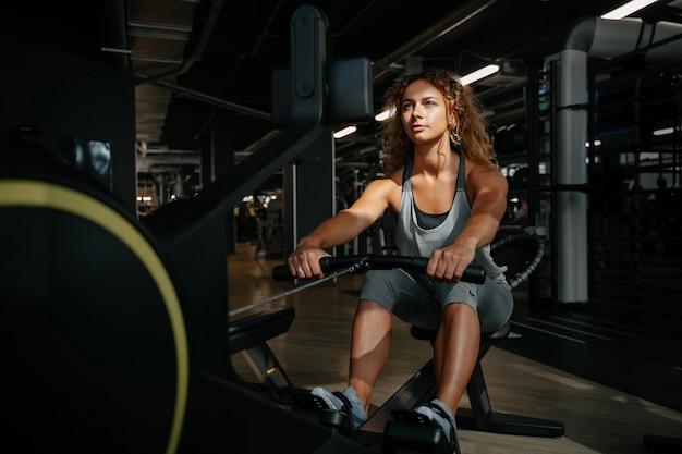 Jonge atletische vrouw houdt zich bezig met fitness op een roeimachine in de sportschool in het zonlichtconcept van...