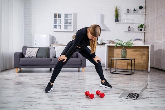 Jonge atletische vrouw in fitness kleding zwarte top en legging in een appartement met behulp van online training van een fitness-site op een laptop en thuis sporten. thuis fitnessen tijdens quarantaine