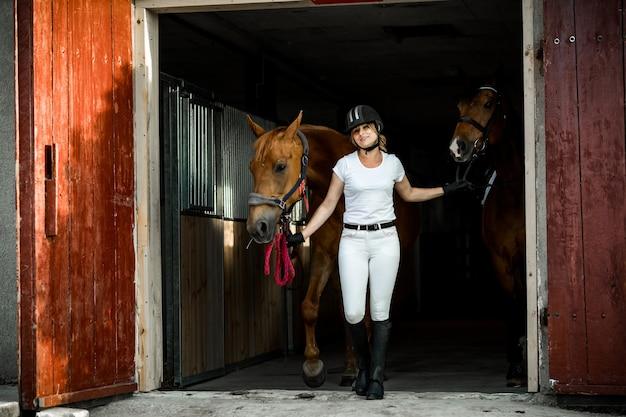 Jonge atletische vrouw in rijkleding neemt twee paarden mee voor een ritje te paard vanuit de stal.