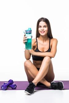 Jonge atletische vrouw in sportkleding, die op vloer zit, drinkwater dat op wit wordt geïsoleerd