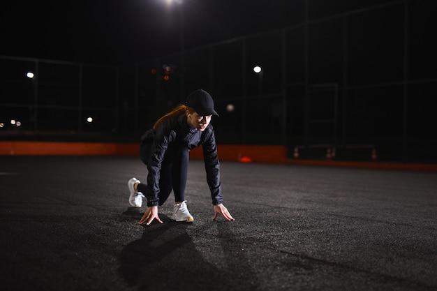 Jonge atletische vrouw in zwart trainingspak en pet staat in de lage startpositie voordat ze...