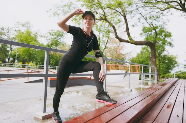 Jonge atletische vrouw in zwart uniform, pet met koptelefoon die naar muziek luistert, sport rekoefeningen doet, warming-up hand in de buurt van pet in stadspark buitenshuis