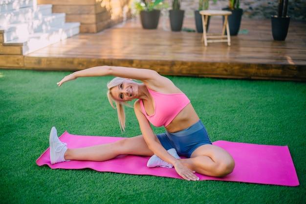 Jonge atletische vrouw voert uitrekkende oefening op groen gazon, concept van gezonde levensstijl