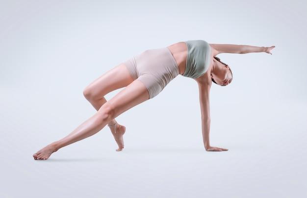 Jonge atletische vrouwentrainer die hatha yoga beoefent, vasishthasana zijplank, balancerende houding om benen en armen te ondersteunen, moderne sportschool, gezond levensstijlconcept. gemengde media
