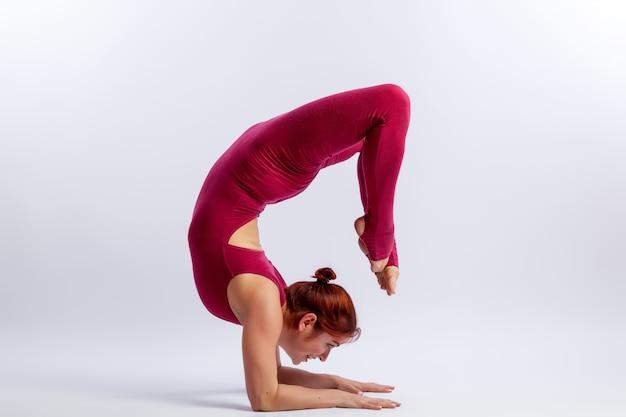 Jonge atletische vrouwenturner in gymnastiek jumpsuit doet zich uitstrekt in moeilijke poses
